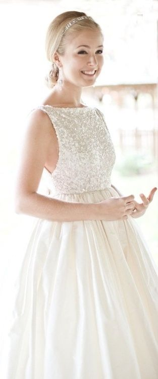 an A-line wedding dress with a white sequin sleeveless bodice with a high neckline and a shiny full skirt is a non-typical solution to rock
