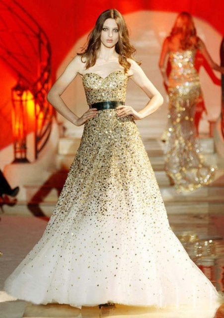 a strapless fully embellished gold sequin wedding dress with an ombre effect and a black leather belt is a bold statement