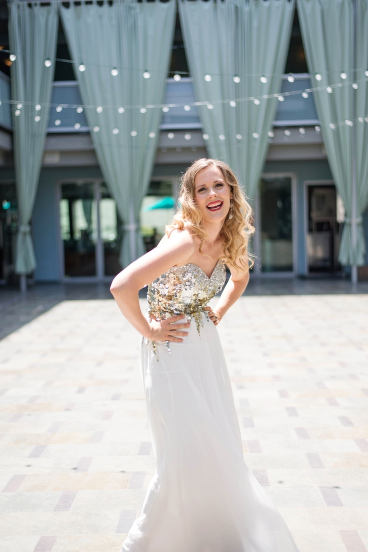 a beautiful modern strapless wedding dress with a gold sequin bodice and a contrasting white skirt is very chic and glam