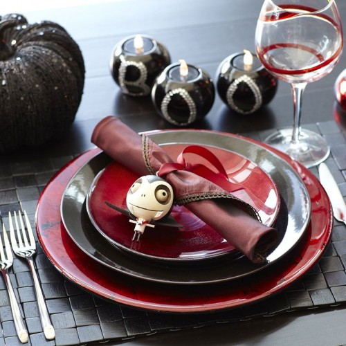 a whimsy Halloween wedding tablescape with BOO candleholders, a black glitter pumpkin, black and red plates and glasses and a woven mat