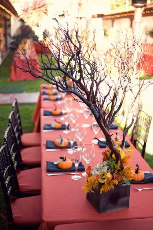 a stylish rustic Halloween wedding tablescape with a red tablecloth, black napkins, pumpkins, a planter with branches and bright blooms and leaves