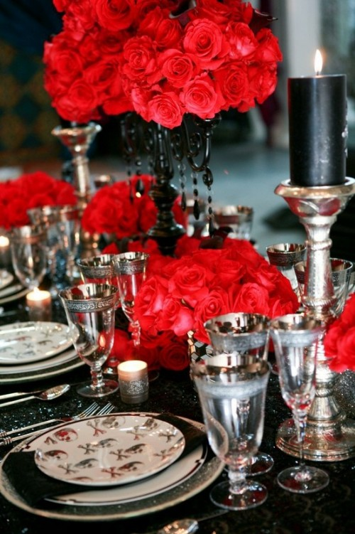a refined Halloween wedding tablescape with a black glitter tablecloth, bright red blooms, chic glasses and candleholders and printed plates