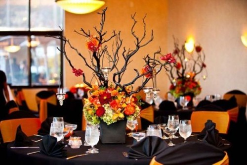 a bold black and orange Halloween wedding tablescape with black napkins, branches in a planter and bold blooms at the base
