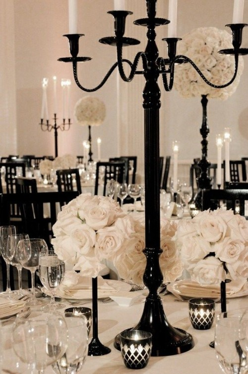 a sophisticated black and white Halloween wedding tablescape with black candleholders and large white rose topiaries, stylish tableware and linens