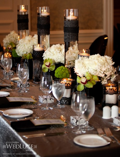 a refined Halloween wedding tablescape with green and white blooms, black lace covering candleholders and vases, neutral plates and a silver tablecloth