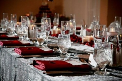 a grey and burgundy Halloween tablescape with elegant glasses, cutlery, and candles is chic and moody