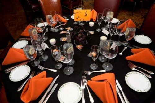 an elegant black, orange and white Halloween wedding tablescape with orange napkins and bold blooms and candles