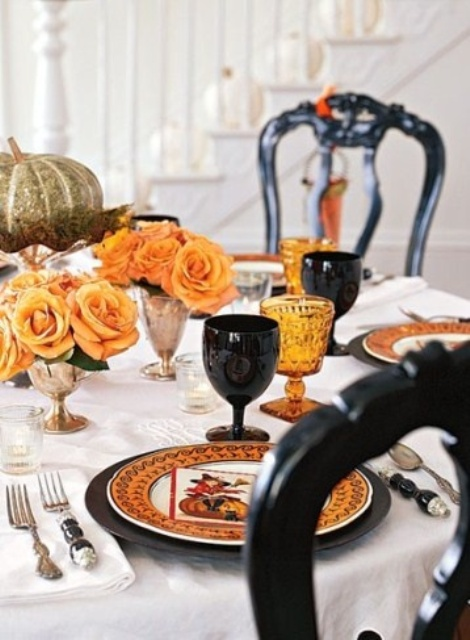 a bold Halloween wedding tablescape with orange blooms, glasses in black and orange, pumpkins and printed plates
