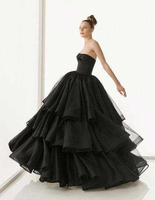 a modern plain black wedding ballown with a strapless bodice and a layered skirt with lots of ruffles for a modern Halloween bride