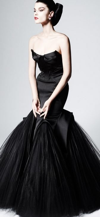 a glossy black strapless mermaid wedding dress with a pointed and bow bodice and a skirt with much tulle is fantastic