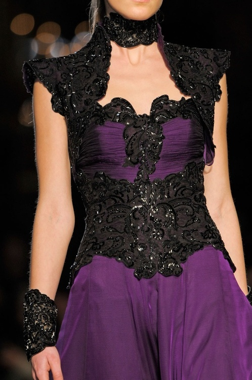 a gorgeous purple wedding dress with shiny black lace and embellishments, catchy shoulders and a neckline