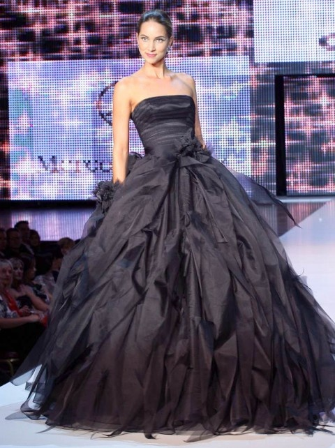 a glossy black strapless wedding ballgown with a tiered skirt and a sleek bodice is a stylish idea for Halloween