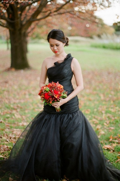 a black one shoulder Halloween wedding dress with a tiered bodice and a tiered skirt is elegant