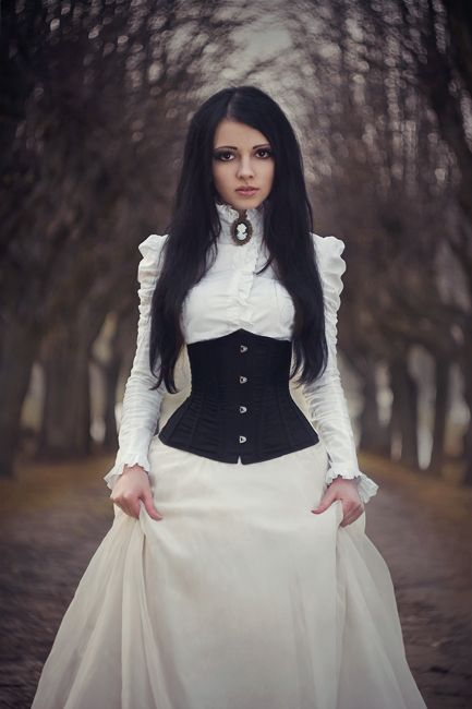 a Victorian white wedding dress with a high neckline and puff sleeves plus a corset looks a bit scary and very stylish