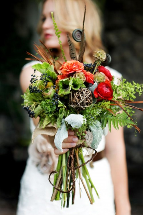 a bright woodland boho wedding bouquet of fern, greenery, berries, bright blooms, feathers, and lotus pieces