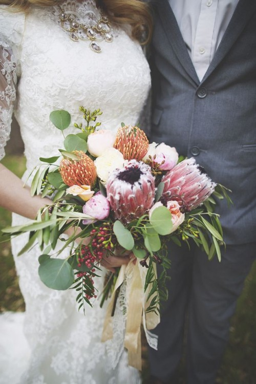 a pretty woodland-inspired wedding bouquet of pink proteas, red pincushion ones, white blooms, berries and various greenery
