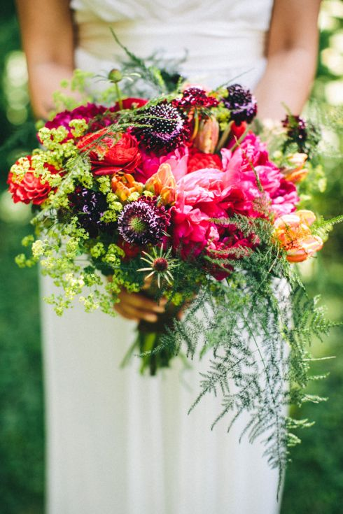 a super bold woodland wedding bouquet with hot pink, red and deep purple blooms, greenery and ferns is a statement for a summer or fall bride