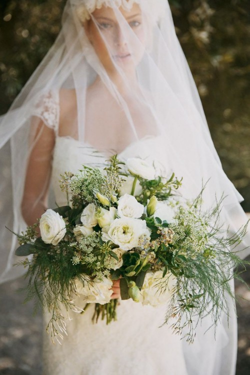 an ethereal wedding bouquet with elegant white ranunculus and various types of greenery is a breezy idea for many weddings