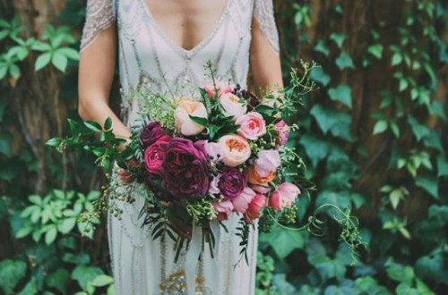 a chic pink and purple wedding bouquet with greenery will fit many colorful weddings including a woodland one