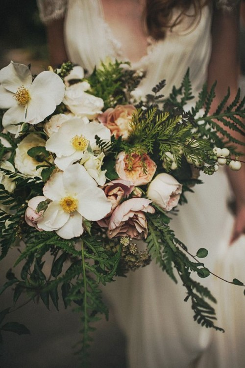 a pastel woodland wedding bouquet with greenery, ferns, white and pink blooms and berries looks very relaxed and spring-like