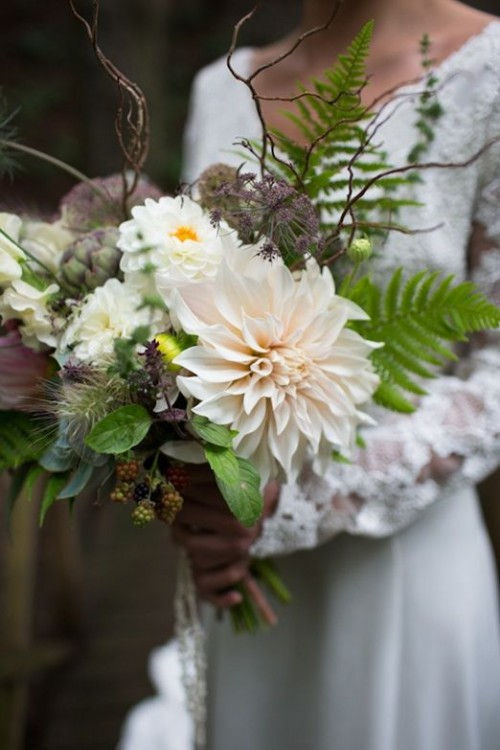 a dimensional wedding bouquet with greenery, white and blush blooms, herbs, berries and twigs looks very forest-like