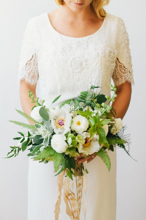 a chic wedding bouquet of various types of greenery and foliage and white blooms plus gold ribbons is wow