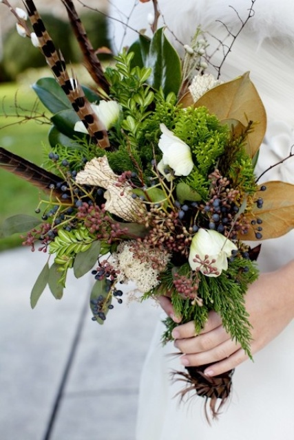 a woodland wedding bouquet of greenery, ferns, berries, white blooms, feathers and large foliage is a bold idea
