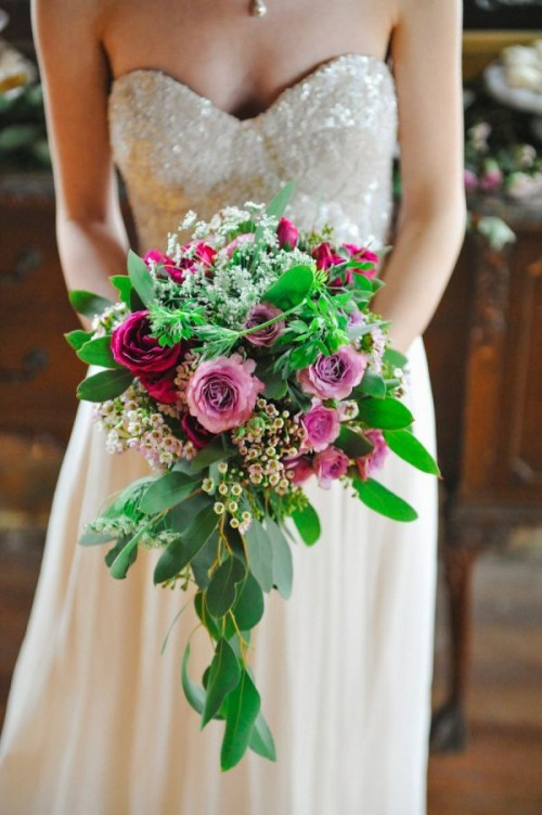 a bold cascading wedding bouquet of pink and fuchsia blooms, white smaller ones and foliage is a stunning idea for a summer bride