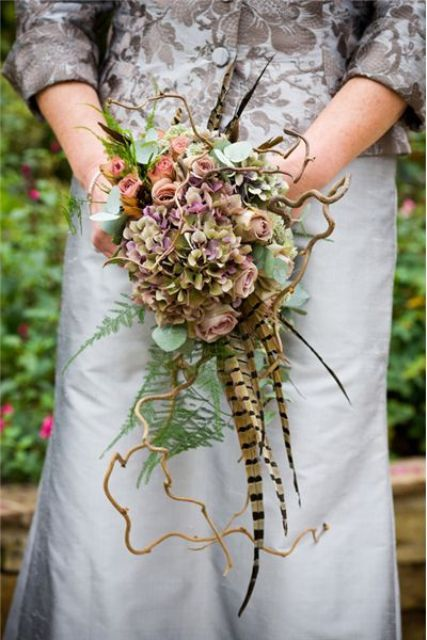 a vintage woodland wedding bouquet with pink, lilac blooms, fern, eucalyptus and twigs and feathers for a forest bride