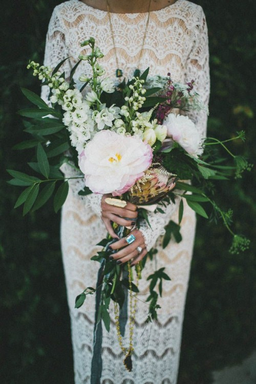 a large and dimensional wedding bouquet with greenery, white and pink blooms, herbs and long gold ribbons with tassels is wow