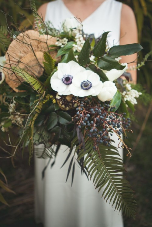 an eye-catchy woodland wedding bouquet with white blooms, privet berries, foliage and twigs is a very catchy dimensional piece
