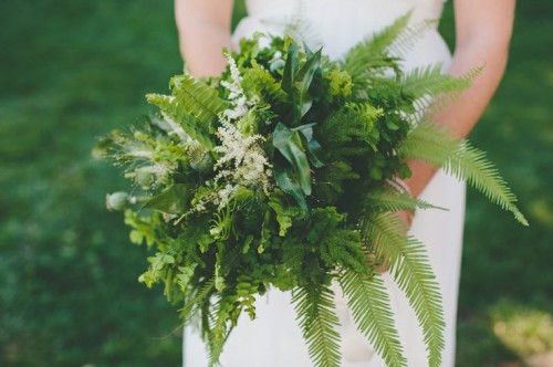 an airy dimensional wedding bouquet of various types of greenery, pink blooms and herbs for a spring or summer forest bride