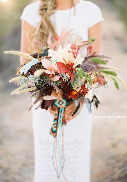 a bold boho forest wedding bouquet with various kinds of foliage, dried leaves and feathers and some boho woven ribbons plus no blooms