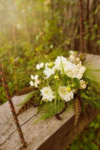 a greenery wedding bouquet with white blooms, berries and feathers is great for summer or fall woodland weddings