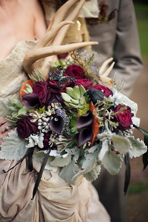 a dark woodland wedding bouquet of deep purple roses and callas, pale greenery, antlers, succulents and antlers for a fall woodland bride