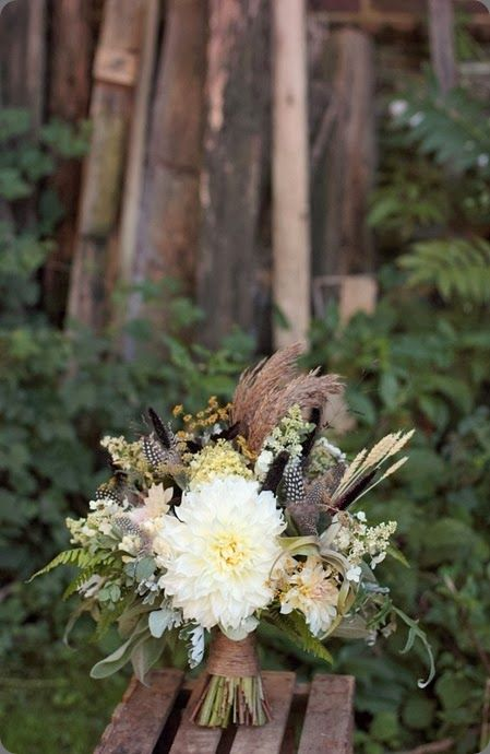 a fall woodland wedding bouquet of white blooms, feathers, ferns and greenery and grasses