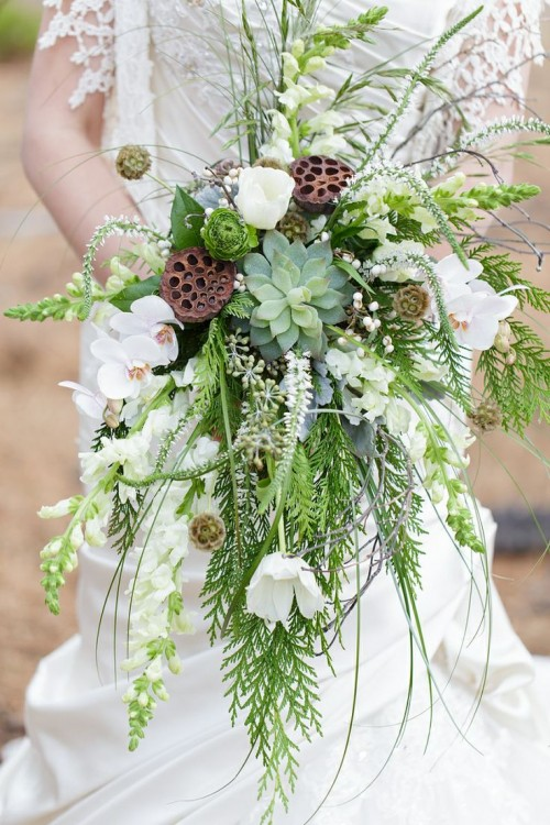 a bold cascading wedding bouquet of various types of greenery, a succulent, white orchids and lotus is great for a woodland wedding