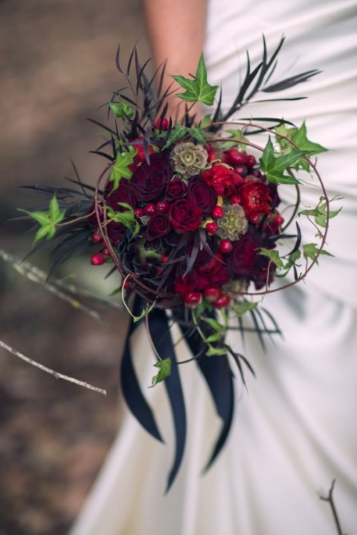 a bold deep red wedding bouquet of blooms, berries and foliage, usual and dark, with black ribbons for a fall bride