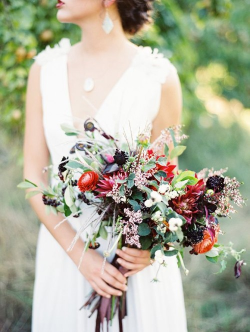 a refined fall wedding bouquet of red and deep purple blooms, greenery and some berries is a pretty and cool idea for a fall woodland wedding
