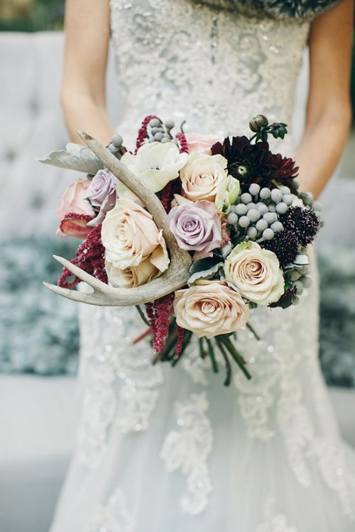 a woodland wedding bouquet with blush and lilac blooms, dark burgundy flowers, antlers and berries is ideal for the fall