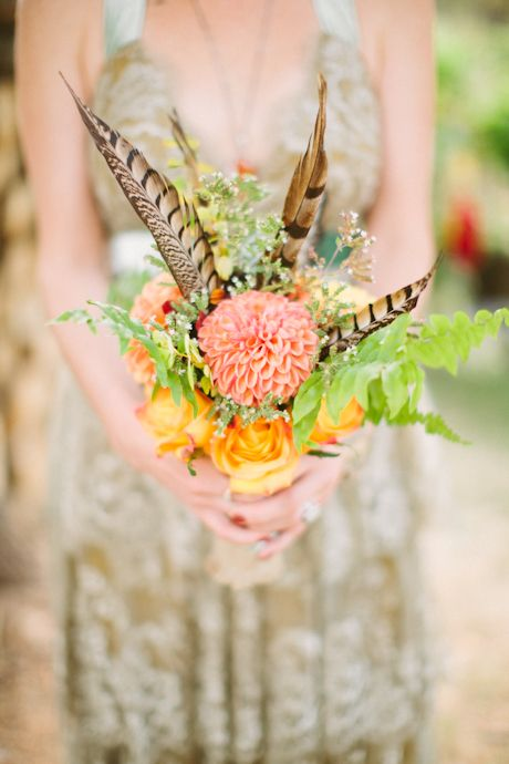 a colorful woodland wedding bouquet with orange and coral blooms, greenery and feathers is a unique option with plenty of color