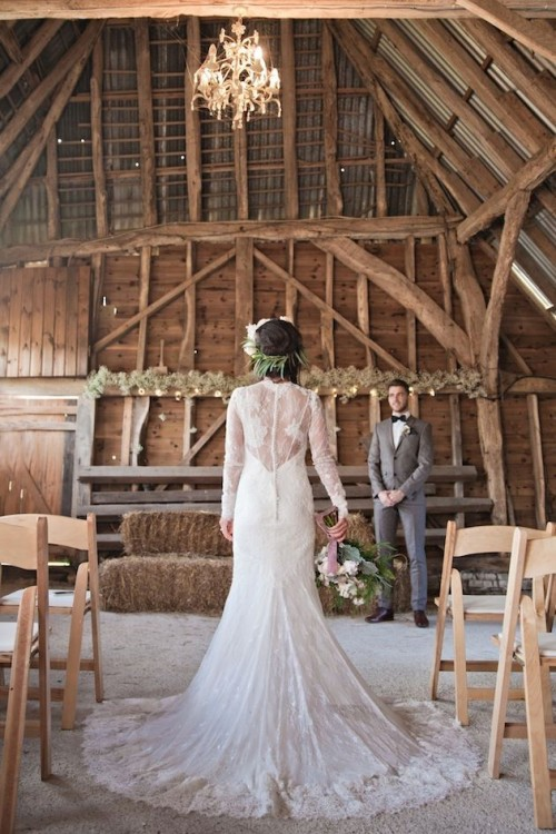 a romantic lace fitting wedding dress with long sleeves, an illusion back and a train