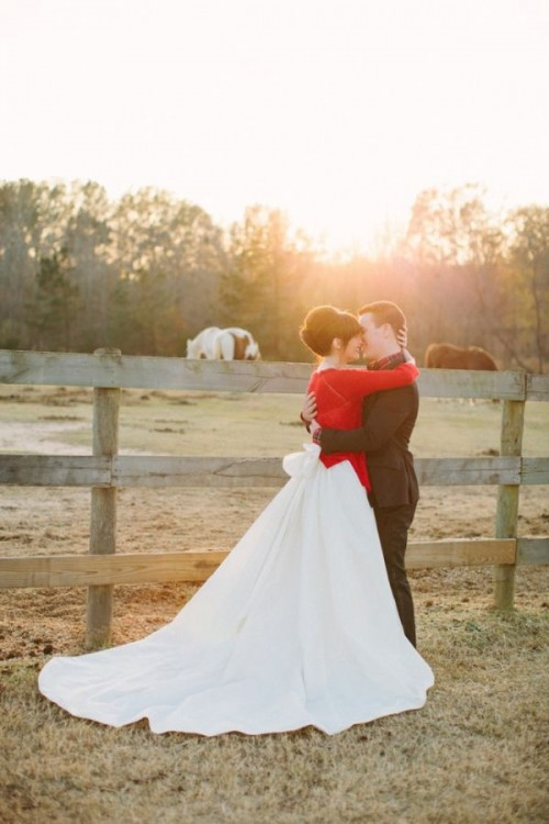 a romantic wedding dress with a large bow on the back and a train plus a red cardigan for a Christmas wedding