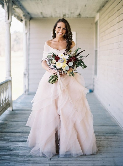a glam and romantic blush strapless wedding dress with a layered skirt with ruffles and a coverup