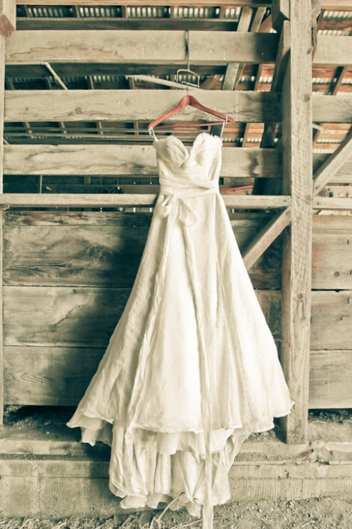 a textural strapless wedding dress with a draped bodice, a sash with a bow and a train