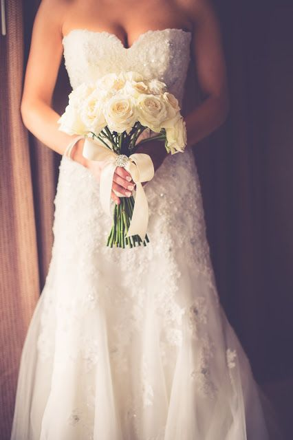 a strapless lace embellished wedding dress and a classic white rose bouquet for a stylish and timeless barn bridal look
