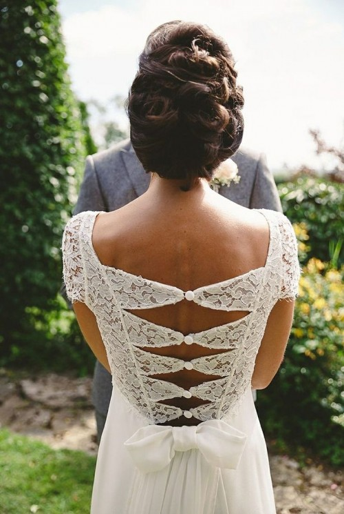 a fitting wedding gown with a lace bodice, cap sleeves and a catchy cutout back on buttons and a plain skirt