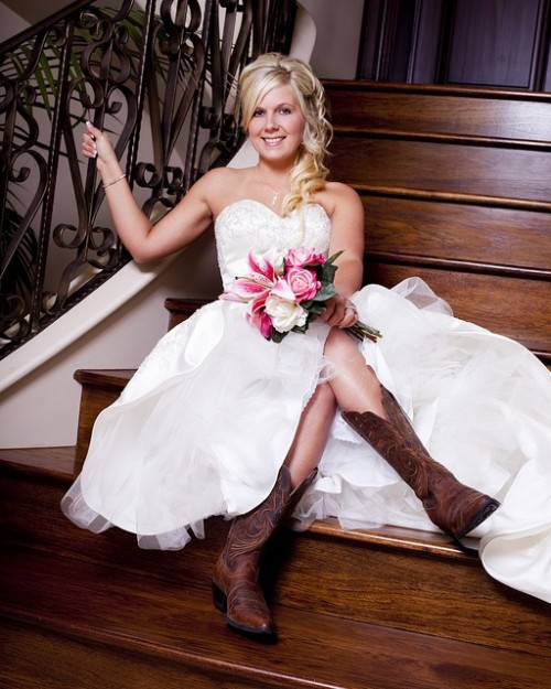 a strapless wedding ballgown of lace with brown cowboy boots for a rustic barn wedding
