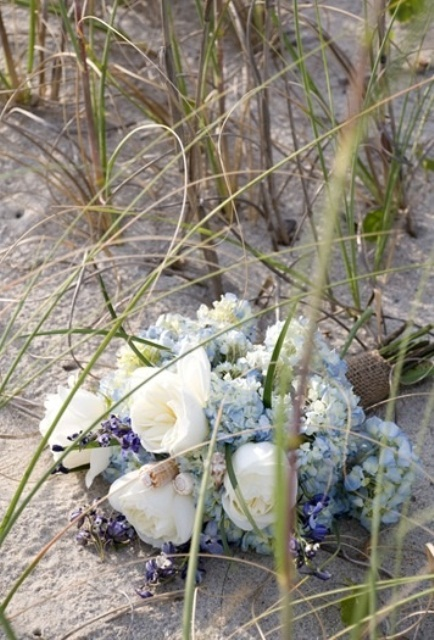 a wedding bouquet of white peonies, blue hydrangeas and seashells for a beach bride