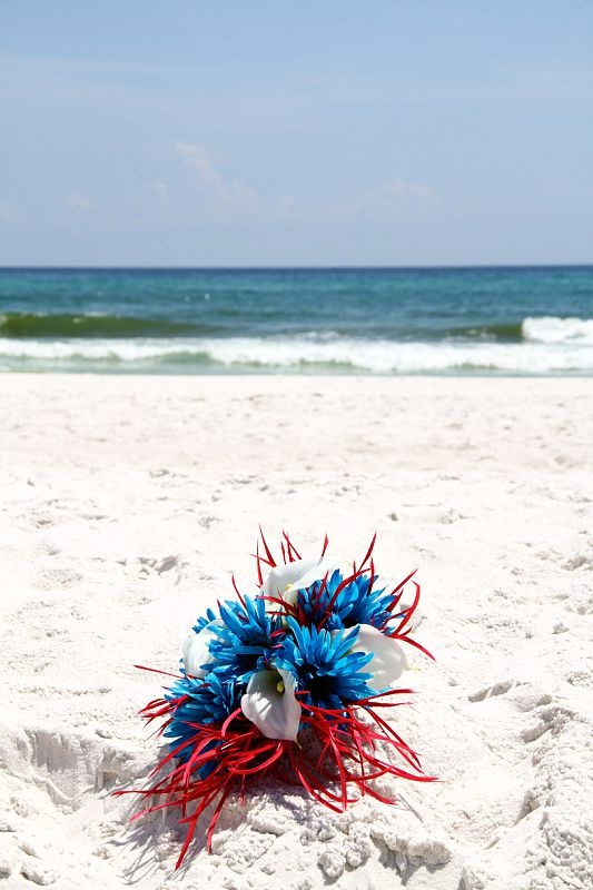 a bright beach wedding bouquet of bright blue and white flowers and red feathers is a bright look
